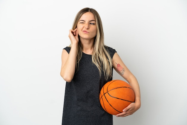Jeune femme jouant au basket-ball sur un mur blanc isolé frustré et couvrant les oreilles