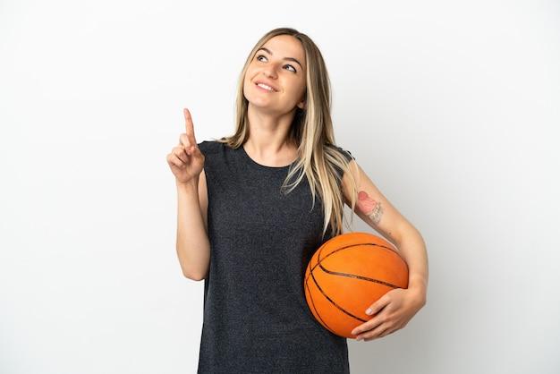 Jeune femme jouant au basket-ball sur un mur blanc isolé montrant une excellente idée