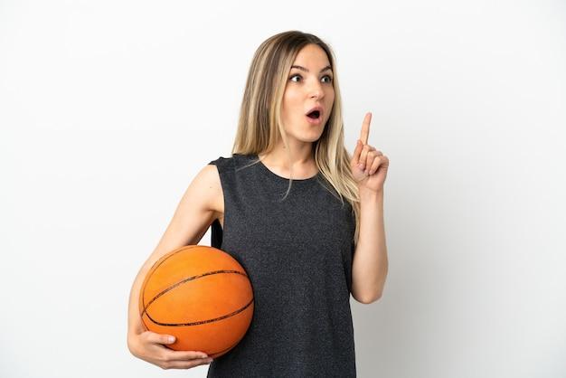 Jeune femme jouant au basket-ball sur un mur blanc isolé pensant à une idée pointant le doigt vers le haut