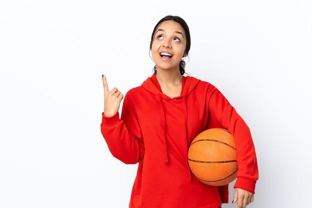 Jeune femme jouant au basket sur fond blanc isolé pointant vers le haut et surpris
