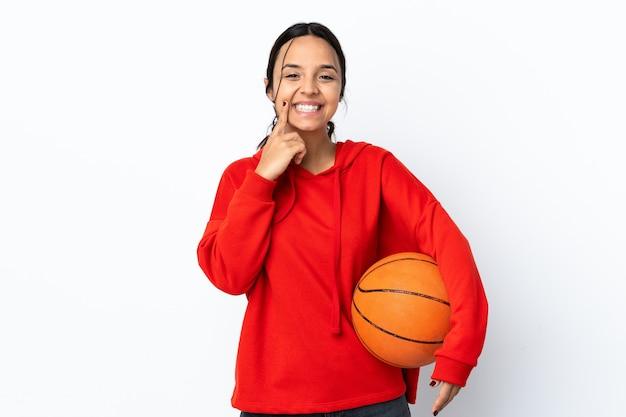 Jeune femme jouant au basket sur mur blanc isolé souriant avec une expression heureuse et agréable