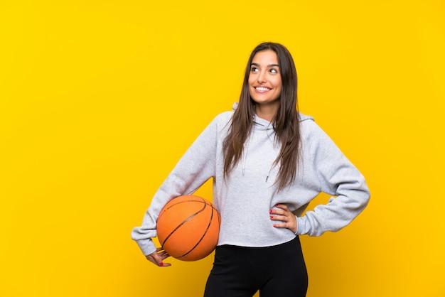 Jeune femme jouant au basketball en levant en souriant
