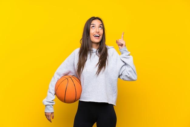 Jeune femme jouant au basketball sur un mur jaune isolé dans le but de réaliser la solution tout en levant un doigt