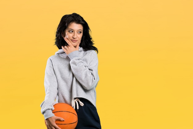 Jeune femme jouant au basketball en pensant à une idée