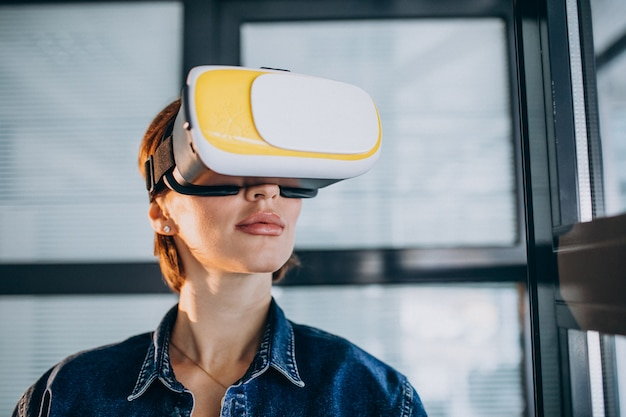Jeune femme jouant au jeu à travers les lunettes de réalité virtuelle