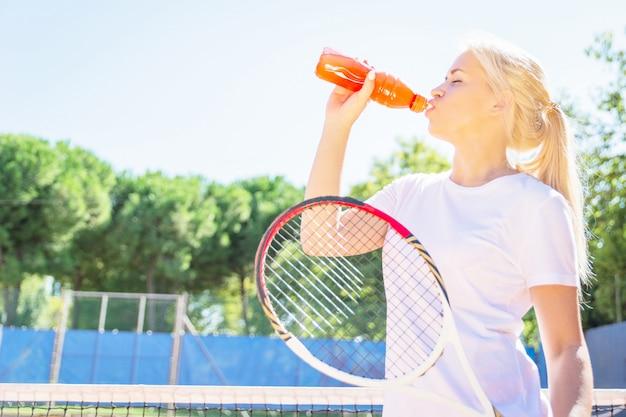 Jeune femme jouant au tennis et à l'eau potable