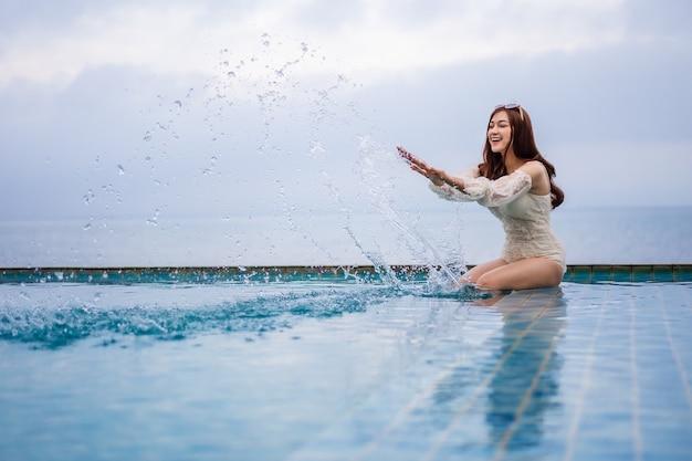 Jeune femme jouant aux éclaboussures d'eau dans la piscine avec fond de mer