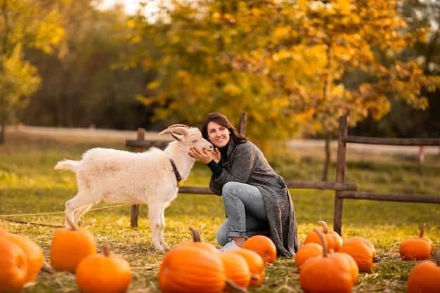Jeune femme jouant avec une chèvre blanche sur une ferme de citrouilles.