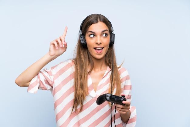 Jeune femme jouant avec un contrôleur de jeu vidéo sur un mur bleu isolé dans le but de réaliser la solution tout en levant un doigt