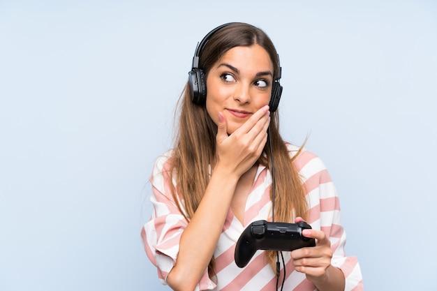 Jeune femme jouant avec un contrôleur de jeu vidéo sur un mur bleu isolé, pensant à une idée