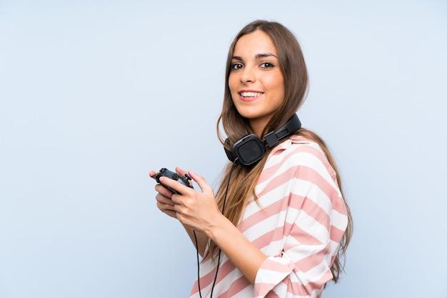 Jeune femme jouant avec un contrôleur de jeu vidéo sur un mur bleu isolé