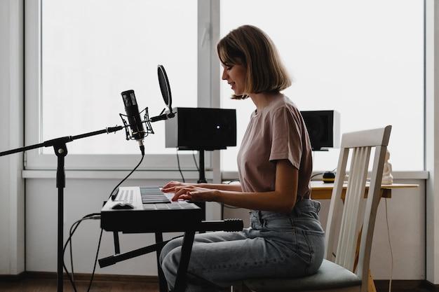 Jeune femme jouant du piano et chantant une chanson à homestudio