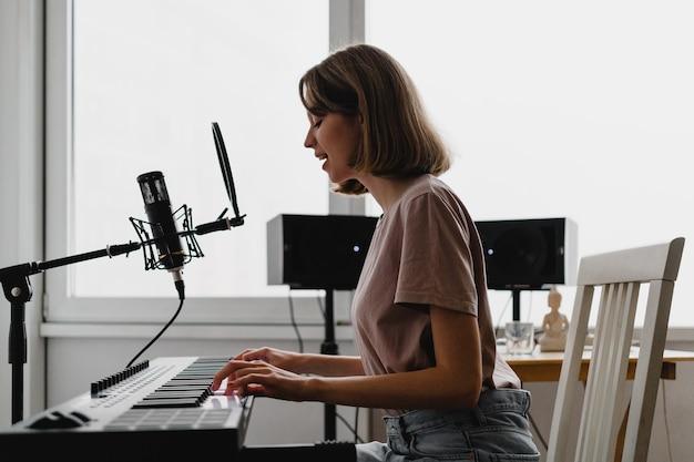 Jeune femme jouant du piano et chantant une chanson à la maison