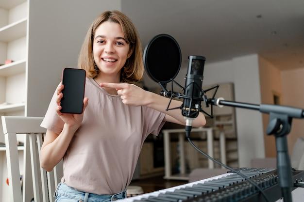 Jeune femme jouant du synthétiseur et chantant la couverture et pointant sur l'application mobile