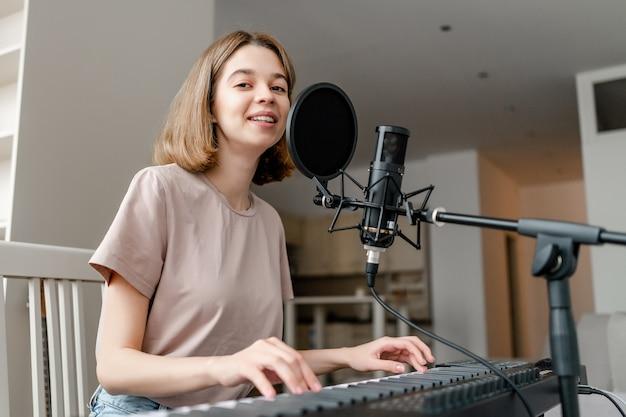 Jeune femme jouant du synthétiseur dans l'appartement