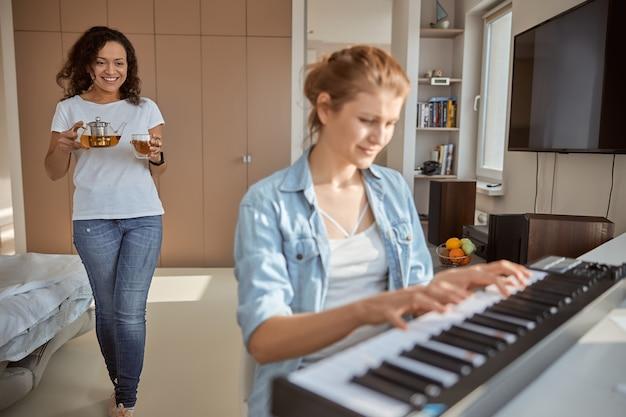 Jeune femme jouant du synthétiseur et profitant de son week-end à la maison