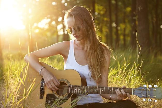 Jeune femme jouant de la guitare dans la nature pendant le coucher du soleil