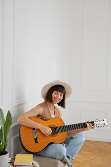 Jeune femme jouant de la guitare à l'intérieur avec espace de copie