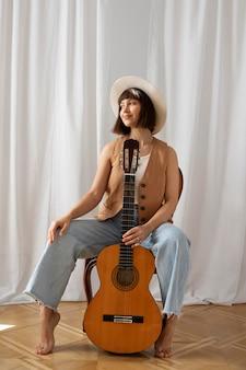 Jeune femme jouant de la guitare à l'intérieur