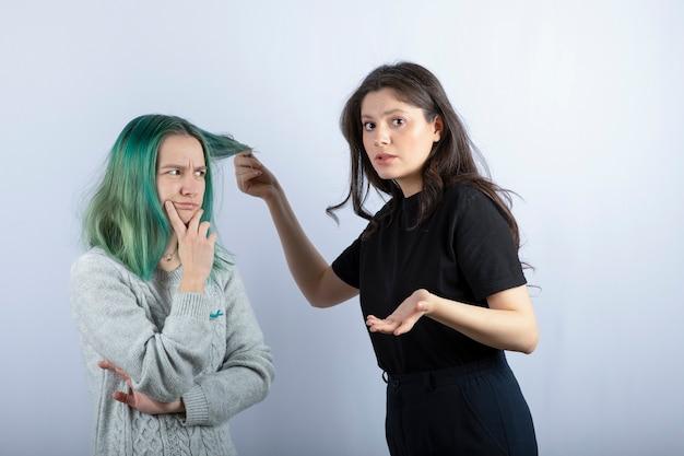 Jeune femme jouant avec son amie sur un mur blanc.