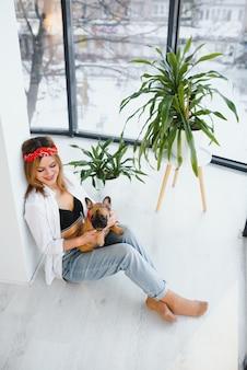 Jeune femme jouant avec son chien à la maison