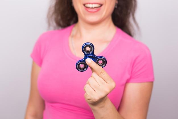 Jeune femme jouant avec un spinner fidget, se concentrer sur le spinner.