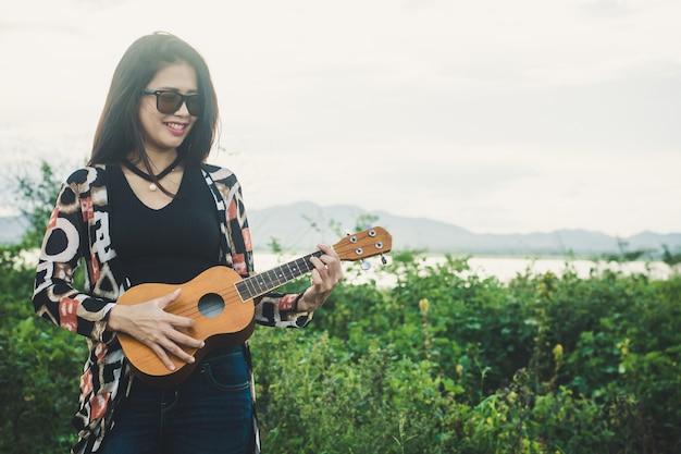 Jeune femme jouant sur un ukulélé brun dans le parc.