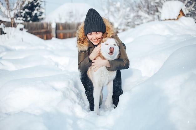 Une jeune femme joue avec le chien husky rouge