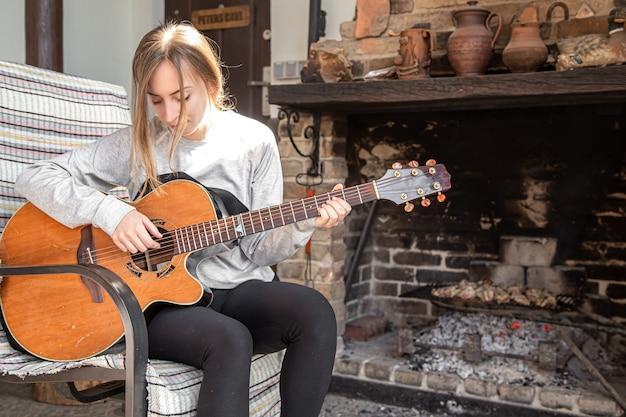 Une jeune femme joue de la guitare dans une ambiance feutrée. le concept de passe-temps et de loisirs.