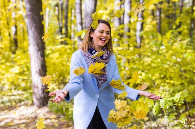 Jeune femme, jouer, à, feuilles automne, dans parc
