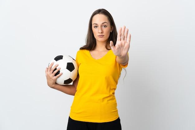 Jeune femme de joueur de football sur fond blanc isolé faisant un geste d'arrêt