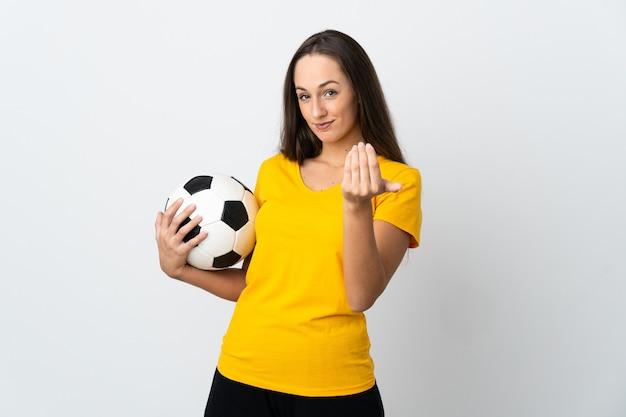 Jeune femme de joueur de football sur fond blanc isolé invitant à venir avec la main. heureux que tu sois venu