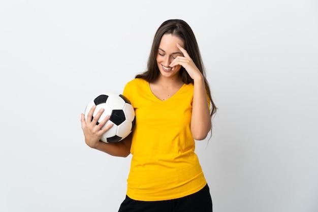 Jeune femme de joueur de football sur fond blanc isolé en riant