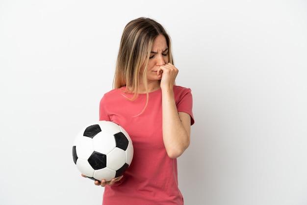 Jeune femme de joueur de football sur un mur blanc isolé ayant des doutes