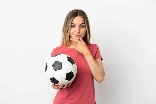 Jeune femme de joueur de football sur mur blanc isolé pensant