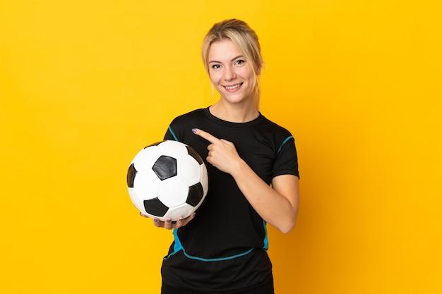 Jeune femme de joueur de football russe isolée sur fond jaune pointant vers le côté pour présenter un produit