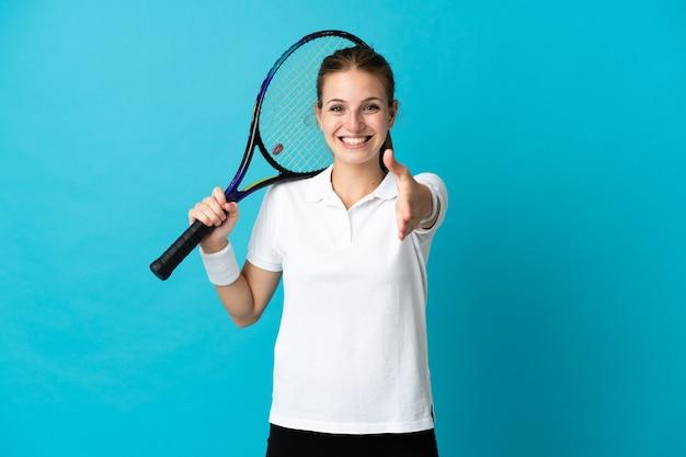 Jeune femme joueur de tennis isolé sur bleu serrant la main pour conclure une bonne affaire