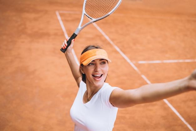 Jeune femme joueuse de tennis sur le court