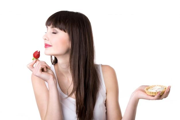 Jeune femme jouissant d'un gâteau