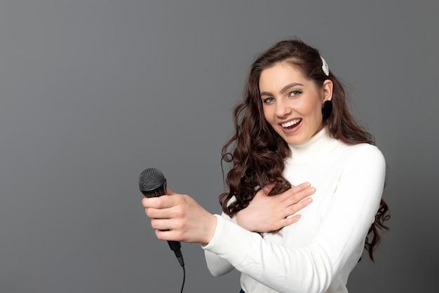 Jeune femme journaliste est debout et étire un microphone vers l'avant, isolé sur fond gris
