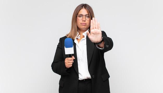 Jeune femme journaliste à la grave, sévère, mécontente et en colère montrant la paume ouverte faisant le geste d'arrêt