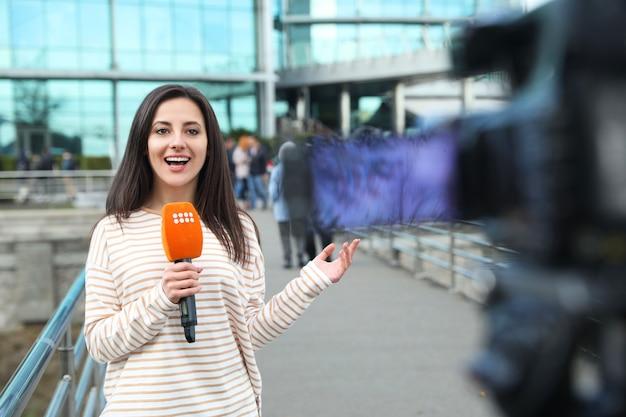 Jeune femme journaliste avec microphone travaillant dans la rue de la ville