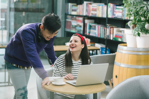 Jeune femme joyeuse assise à la table avec un ordinateur portable dessus et regardant son amie asiatique debout à ses côtés