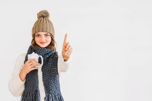Jeune femme joyeuse en bonnet et écharpe avec une tasse de boisson montrant le doigt