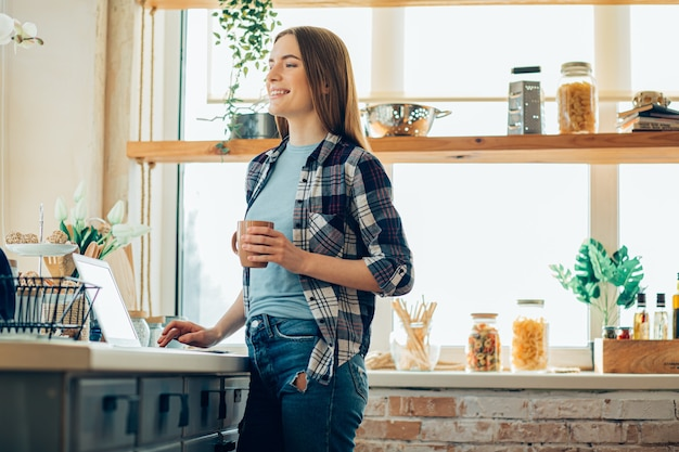 Jeune femme joyeuse debout dans la cuisine avec une tasse et à l'écart