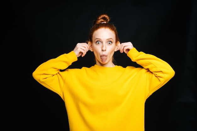 Jeune femme joyeuse folle en pull jaune touchant les oreilles avec les mains et tirant la langue