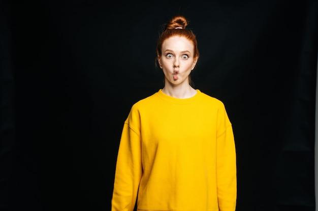 Jeune femme joyeuse folle en pull s'amusant en faisant des lèvres de poisson sur fond noir isolé