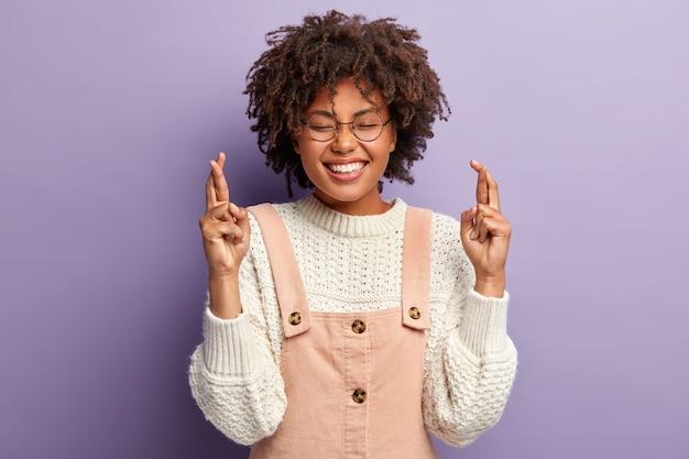 Jeune femme joyeuse garde les doigts croisés, espère le meilleur, sourit largement, porte un pull blanc et une salopette, fait des vœux, prie pour les parents, veut atteindre l'objectif, isolé sur un mur violet