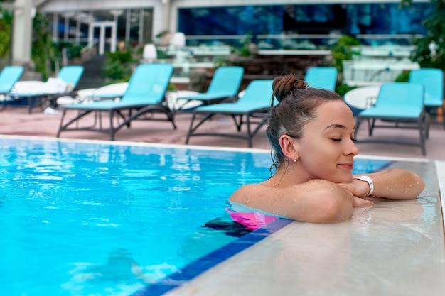 Jeune femme joyeuse heureuse avec les yeux fermés profitant de la baignade dans une piscine tout en vous relaxant dans une station thermale de bien-être
