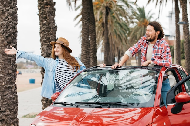 Jeune femme joyeuse et homme se penchant de voiture